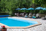 Swimming pool with plenty of loungers and sun shades0